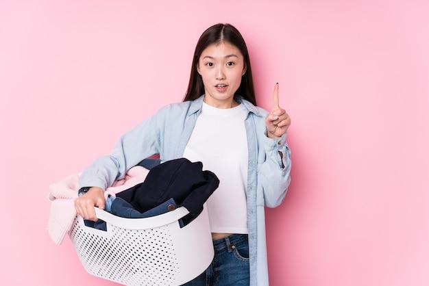 Młoda chińska kobieta podnosi up brudni ubrania odizolowywających mieć niektóre doskonałego pomysł, pojęcie twórczość.