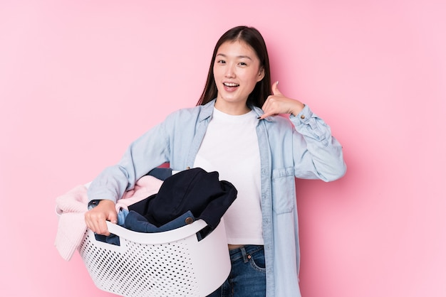 Młoda chińska kobieta podnosi up brudni ubrania odizolowywających pokazywać gesta telefonu komórkowego gesta palcami.