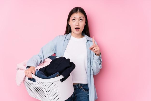Młoda chińska kobieta podnosi up brudni ubrania odizolowywał wskazywać do góry z rozpieczętowanym usta.