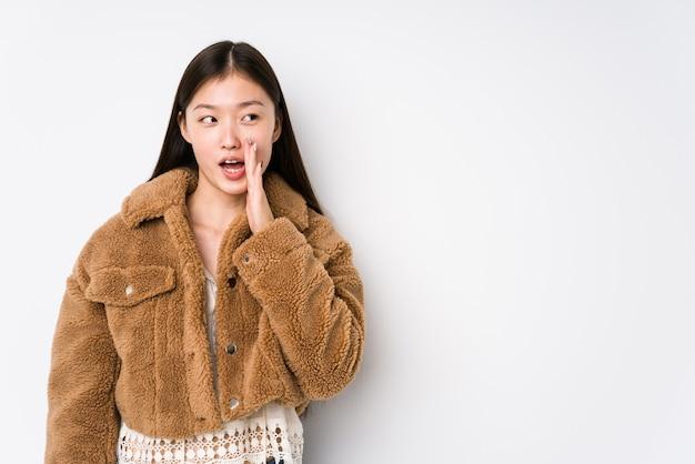 Młoda chińska kobieta pozuje w białej ścianie mówi tajną gorącą hamującą wiadomość i patrzeje na boku