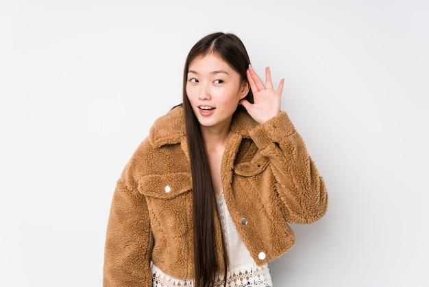 Młoda chińska kobieta pozuje w białej ścianie odizolowywał próbować słuchać plotki.