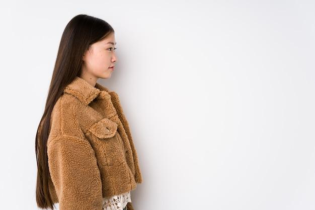 Młoda chińska kobieta pozuje w białej ścianie odizolowywał wpatrujący się z lewej strony, z ukosa pozy.