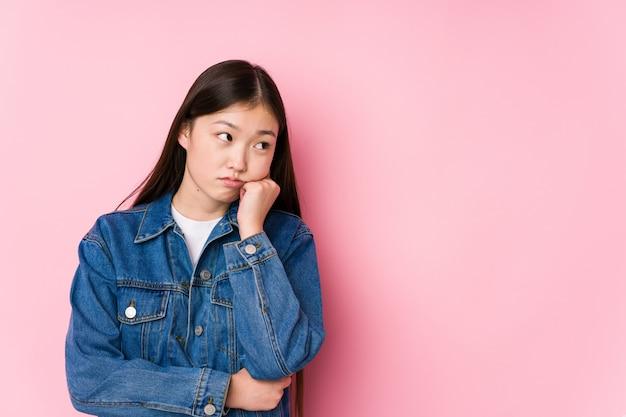 Młoda chińska kobieta pozuje w różowej ścianie która czuje smutny i zadumany