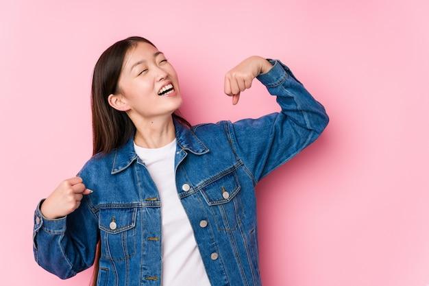 Młoda chińska kobieta pozuje w różowym tle odizolowywał dźwiganie pięść po zwycięstwa, zwycięzcy pojęcie.
