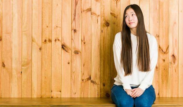 Młoda chińska kobieta siedzi na drewnianym miejscu marzy o osiągnięciu celów i zamierzeń