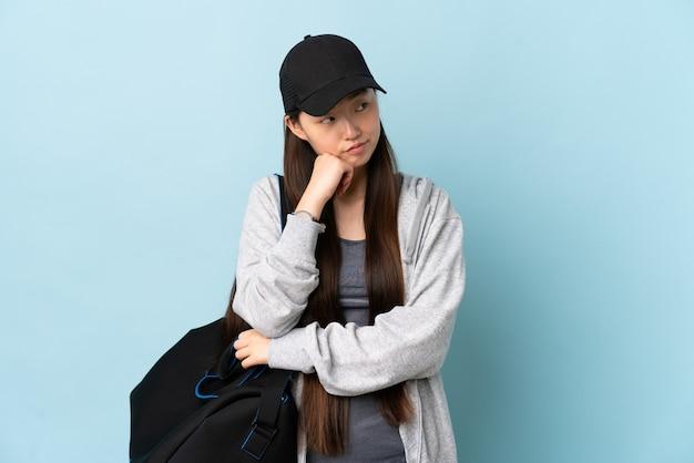 Młoda chińska kobieta sportu z torbą sportową na odizolowanych niebieskiej ścianie z wypowiedzi zmęczony i znudzony