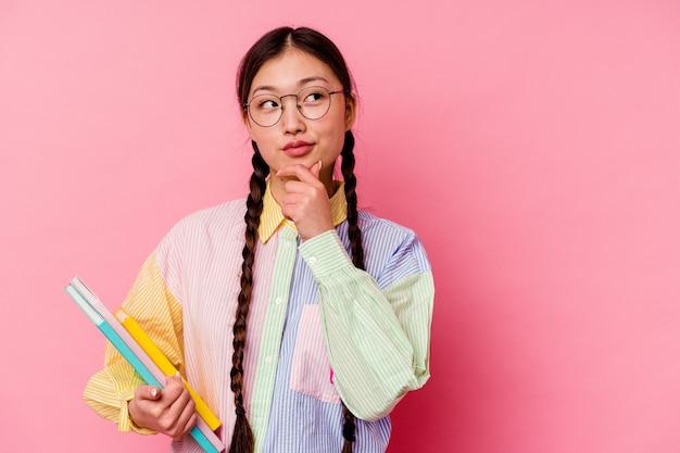 Młoda chińska kobieta studentka trzyma książki ubrana w modną wielokolorową koszulę i warkocz, na białym tle na różowym tle, patrząc w bok z wyrazem wątpliwości i sceptyczny.