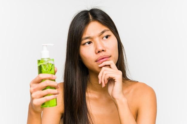 Młoda chińska kobieta trzyma moisturizer z aloesem odizolowywał patrzeć z ukosa z wątpliwym i sceptycznym wyrażeniem.