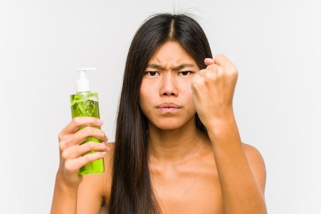 Młoda chińska kobieta trzyma moisturizer z aloesem odizolowywał pokazywać pięść z agresywnym wyrazem twarzy.