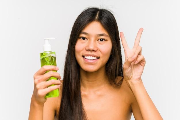 Młoda chińska kobieta trzyma moisturizer z aloesem odizolowywał pokazywać zwycięstwo znaka i uśmiecha się szeroko.