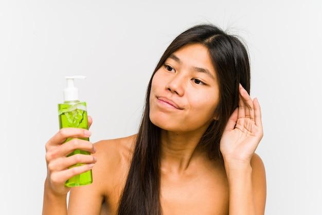 Młoda chińska kobieta trzyma moisturizer z aloesem vera próbuje słuchać plotki.