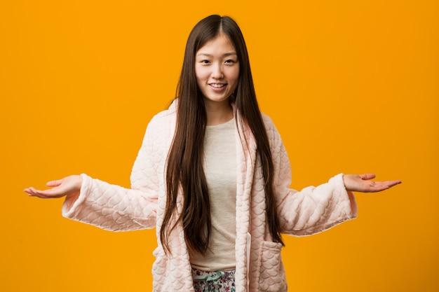 Młoda chińska kobieta w piżamie pokazuje mile widziany wyrażenie.