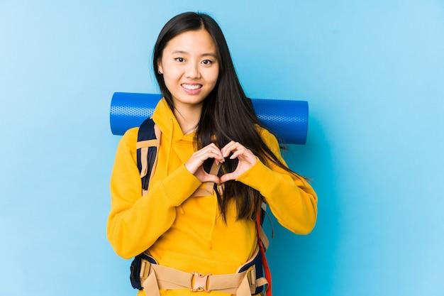 Młoda chińska kobieta z plecakiem na białym tle, uśmiechając się i pokazując kształt serca rękami.