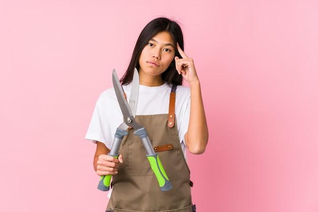 Młoda chińska ogrodniczki kobieta trzyma nożyce odizolowywającą wskazuje świątynię z palcem, główkowanie, skupiający się na zadaniu.