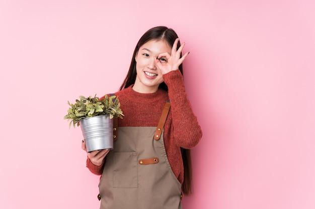 Młoda chińska ogrodniczki kobieta trzyma rośliny odizolowywał z podnieceniem utrzymuje ok gest na oku.