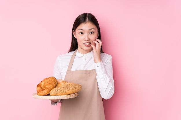 Młoda chińska piekarz na białym tle gryząc paznokcie, nerwowa i bardzo niespokojna.