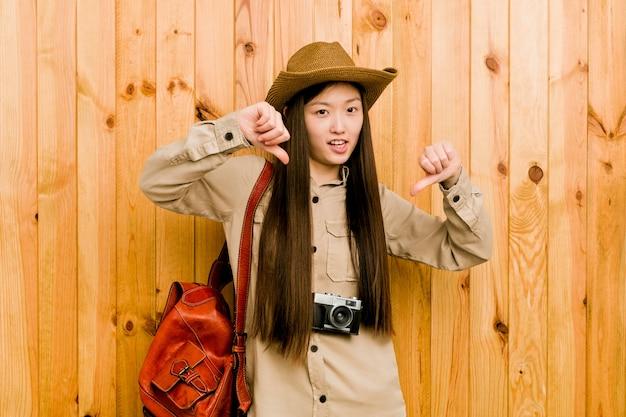 Młoda chińska podróżnicza kobieta pokazuje kciuka puszek i wyraża niechęć