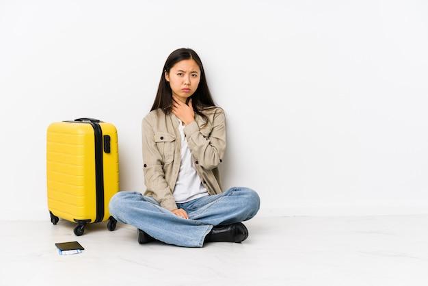Młoda chińska podróżnicza kobieta siedząca trzyma kartę pokładową cierpi ból gardła z powodu wirusa lub infekcji.
