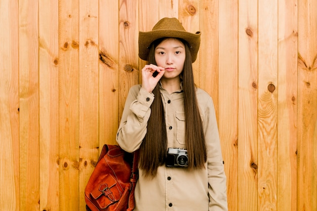 Młoda chińska podróżnicza kobieta trzyma sekret z palcami na wargach.