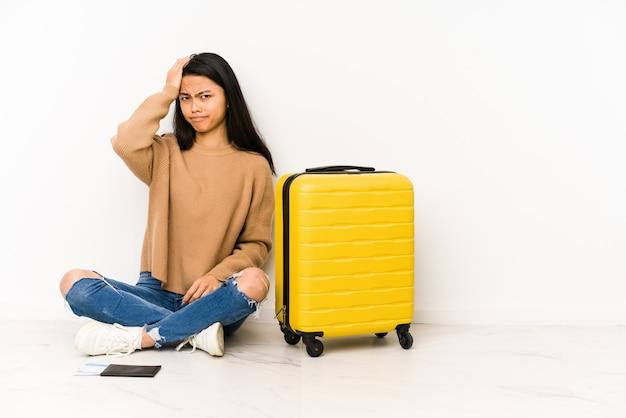 Młoda chińska podróżniczka siedząca na podłodze z zszokowaną walizką przypomniała sobie ważne spotkanie.