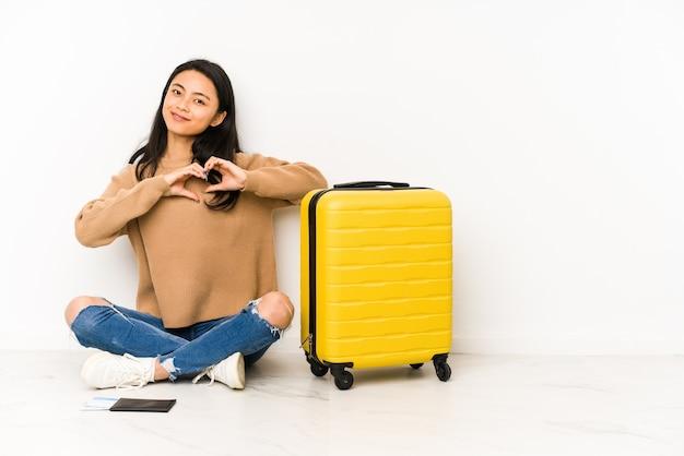 Młoda chińska podróżniczka siedzi na podłodze z walizką na białym tle, uśmiechając się i pokazując kształt serca rękami.