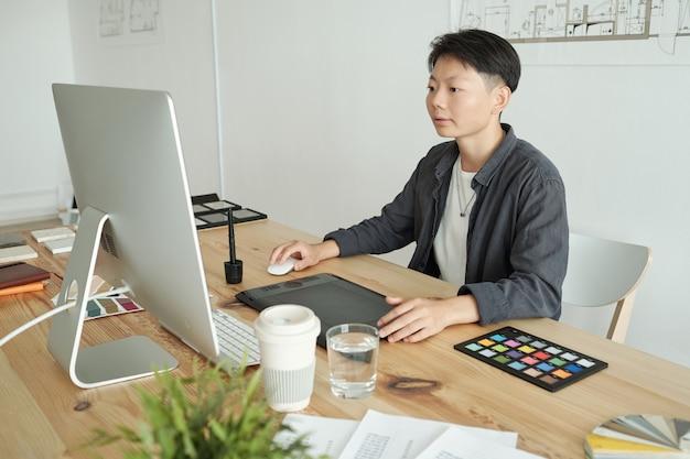 Młoda chińska projektantka siedząca przed monitorem komputera
