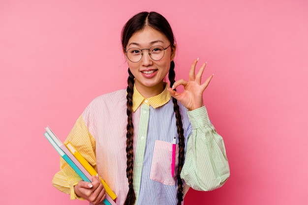 Młoda chińska studentka trzyma książki ubrana w modną wielokolorową koszulę i warkocz, na białym tle na różowym tle wesoły i pewny siebie, pokazując ok gest.