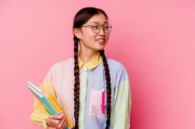 Młoda chińska studentka trzymająca książki ubrana w modną wielokolorową koszulę i warkocz, na białym tle na różowym tle wygląda na bok uśmiechnięta, wesoła i przyjemna.