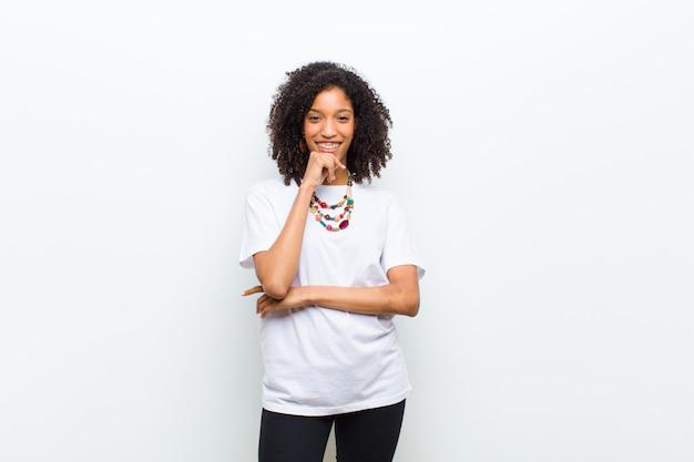 Młoda chłodno amerykanin afrykańskiego pochodzenia kobieta patrzeje szczęśliwy i uśmiechnięty z ręką na podbródku, zastanawiający się pytanie lub pytający, porównujący opcje