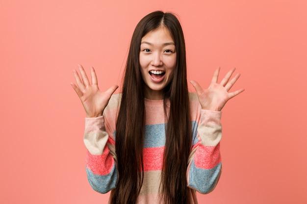 Młoda chłodno chińska kobieta świętuje zwycięstwo lub sukces
