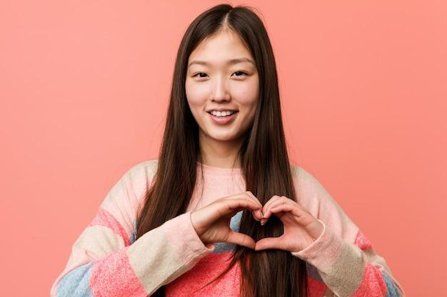 Młoda chłodno chińska kobieta uśmiecha się kierowego kształt z on i pokazuje ręki.