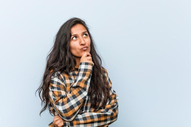 Młoda chłodno indyjska kobieta patrzeje z ukosa z wyrażającym wątpliwości i sceptycznym wyrazem twarzy.