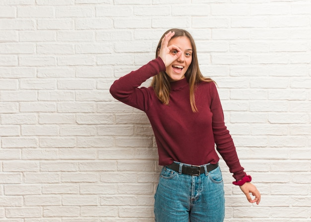 Młoda chłodno kobieta nad cegły ścianą ufną robi ok gestowi na oku