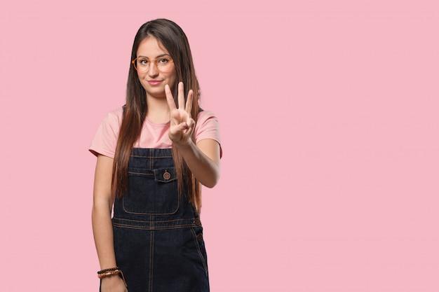 Młoda chłodno kobieta pokazuje liczbę trzy