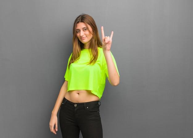 Młoda chłodno rosyjska dziewczyna robi rockowemu gestowi