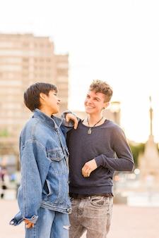Młoda, chłopczyca para lesbijek, androgyniczna niebinarna osoba transpłciowa i latynoska kobieta z krótkimi włosami