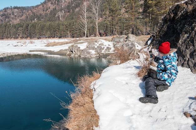 Młoda chłopiec bierze fotografie na brzegowej rzece