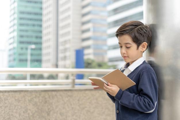 Młoda chłopiec czyta książki na dzielnicie biznesu miastowej, edukaci pojęcie