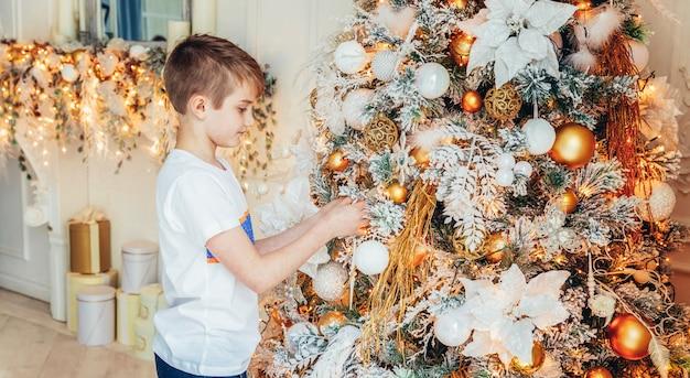 Młoda chłopiec dekoruje choinki w wigilię w domu. dzieciak w lekkiej sypialni z zimową dekoracją. czas na uroczystość koncepcji banner