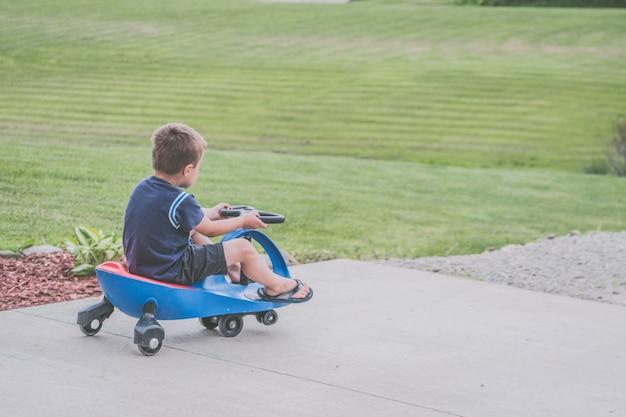 Młoda chłopiec jedzie błękitnego i czerwonego wiggle samochód na popielatym cemencie w parku