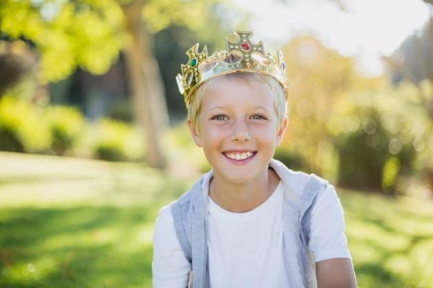 Młoda chłopiec jest ubranym koronę i ono uśmiecha się w parku