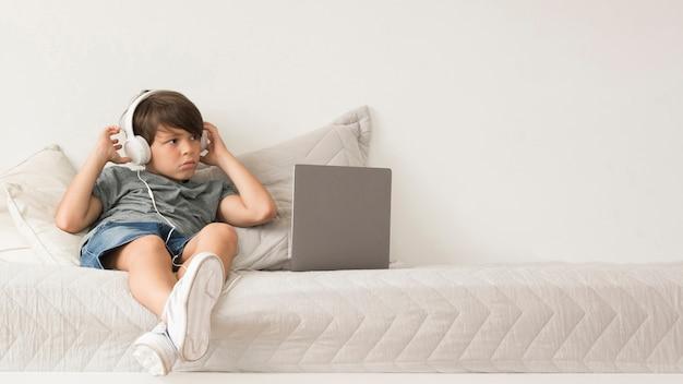 Młoda chłopiec patrzeje na laptopie