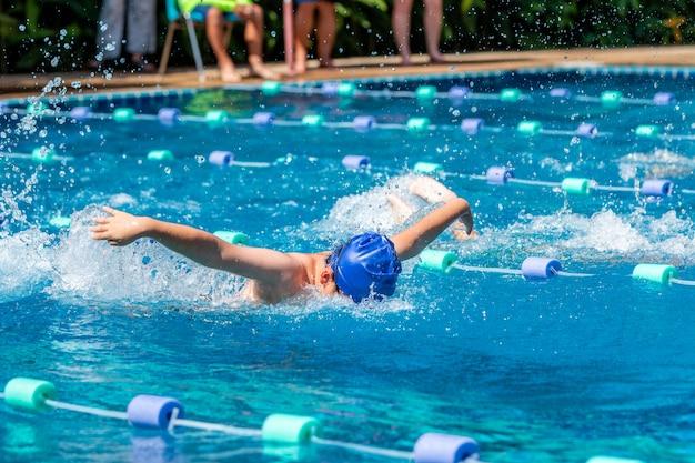 Młoda chłopiec pływaczka robi motyliego uderzenia przy basenem