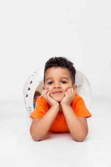 Młoda chłopiec pozuje podczas gdy bawić się w domu