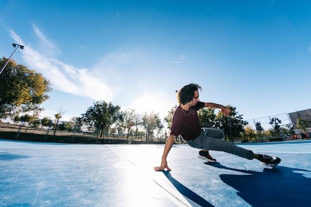 Młoda chłopiec tanczy i pozuje przy boisko do koszykówki