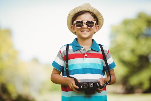 Młoda chłopiec trzyma kamerę w okularach przeciwsłonecznych