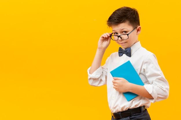 Młoda chłopiec trzyma książkę z szkłami