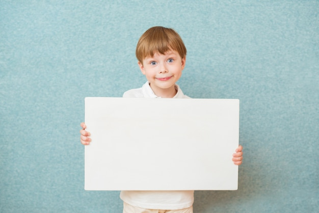 Młoda chłopiec uśmiecha się białego pustego plakat i trzyma