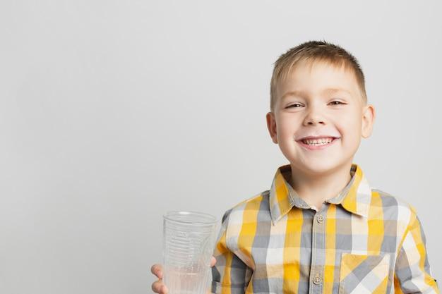 Młoda chłopiec uśmiecha się dojnego szkło i trzyma