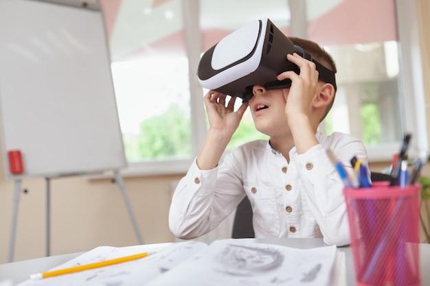 Młoda chłopiec używa 3d rzeczywistości wirtualnej słuchawki przy szkołą